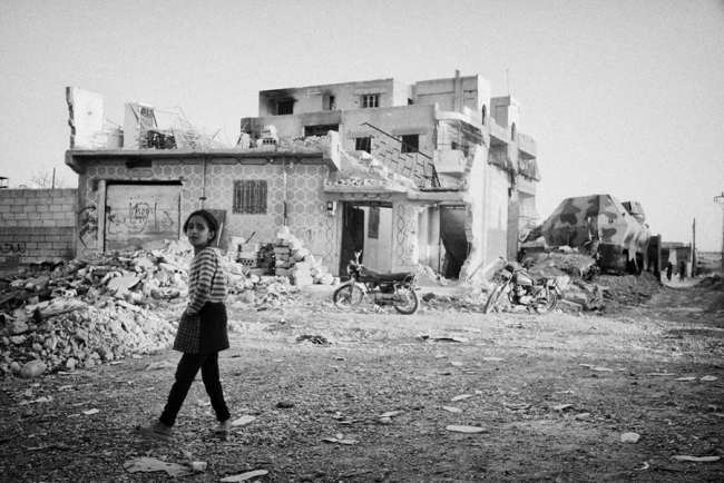 A young Syrian girl stands on a ruined street. Photo: Eddy Van Wessel/MSF