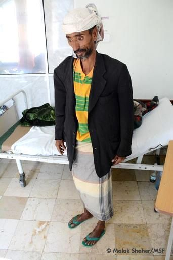 Abdurrahman stands by his hospital bed