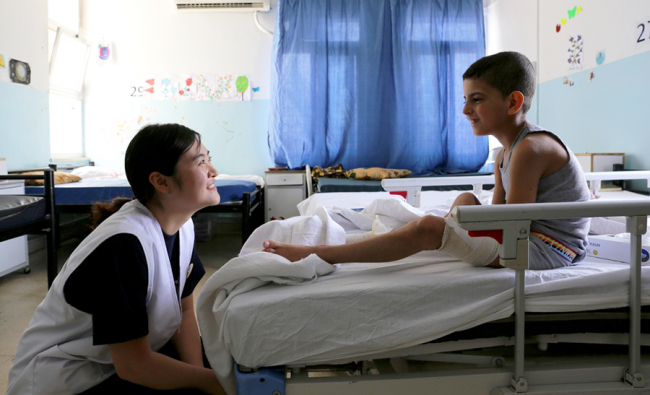 An MSF nurse with a young Syrian boy who was being treated at Ramtha. Photo: Joosarang Lee/MSF