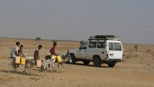 Four children ride donkeys as they go to collect water in Yemen.
