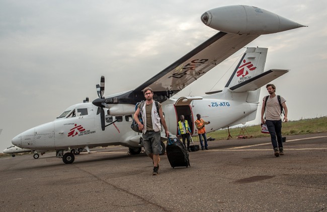 Image shows MSF staff at the airport in Bangui, disembarking a small plane