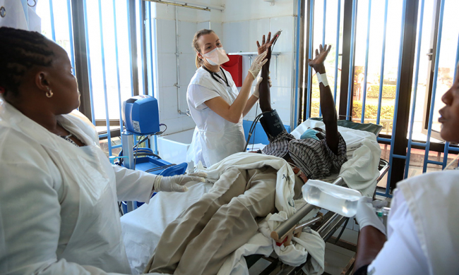Image shows a Caroline examining a male patient, who lies on a hospital bed with his arms raised.