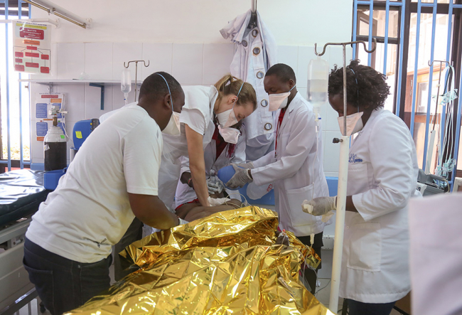 Image shows the team trying to rususcitate a figure wrapped in a gold survival blanket