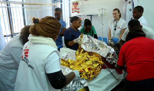Image shows the team trying to resuscitate a figure wrapped in a gold survival blanket. Caroline supervises