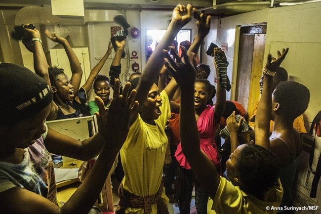 Women raise their arms and sing with joy on board the ship