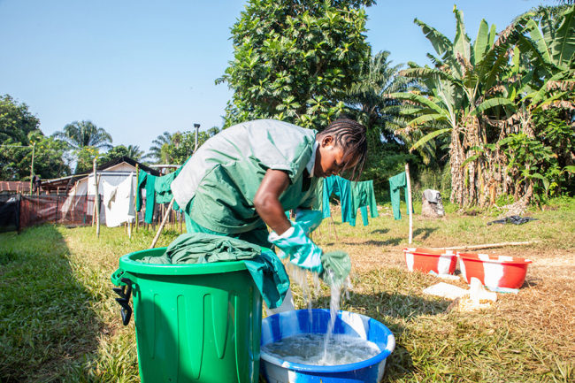 A member of MSF's hygiene team disinfects the team's clothes. Photo: Louise Annaud/MSF