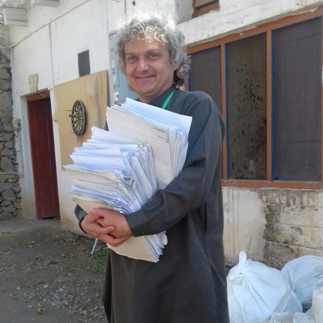 Eben holds an enormous stack of papers