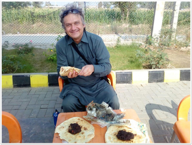 Image shows Eben, wearing his salwar kameez, eating a hearty lunch in Pakistan