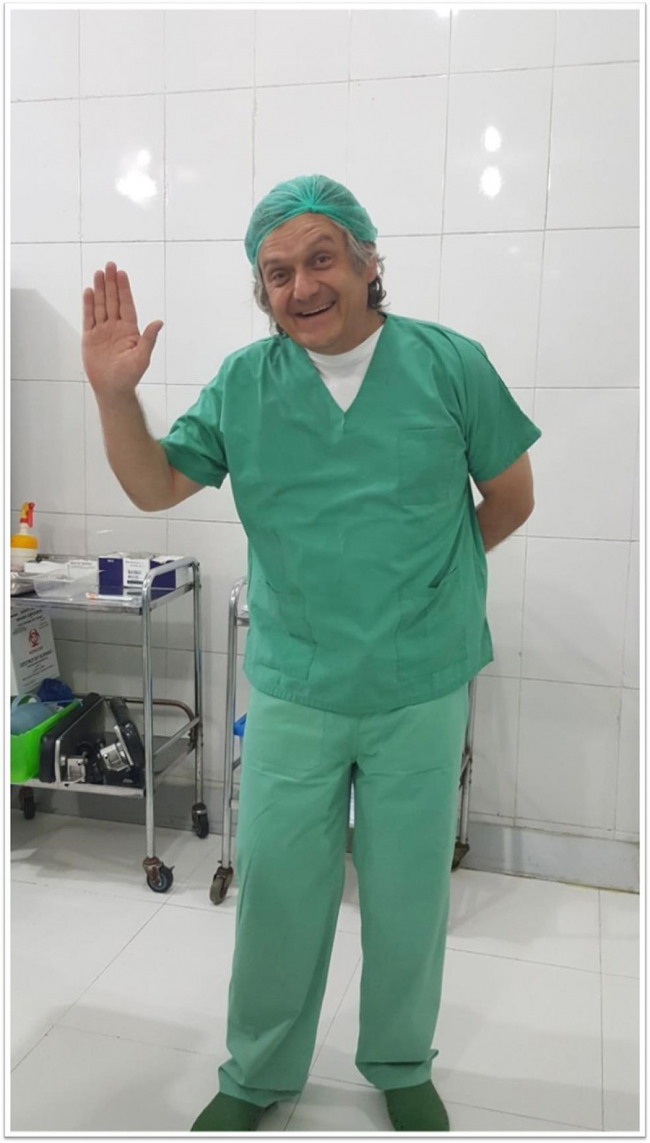 Image shows Eben, wearing hospital scrubs, waving at the camera