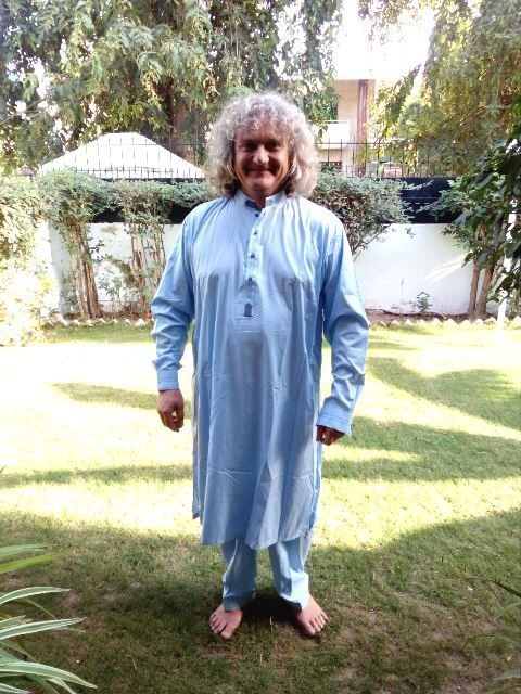 Image shows Eben smiling in his pale blue shalwaar kameez, which he wears in a light-filled garden