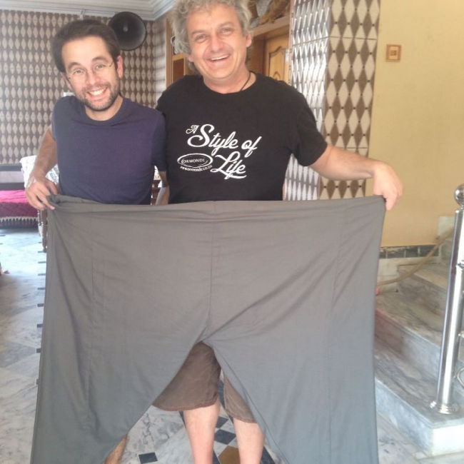 Image shows Eben and a colleague holding up a pair of trousers wide enough to fit them both!