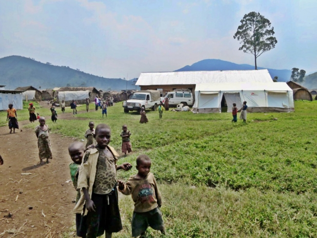 Landcruisers, tents and curious children at one of the mobile clinics