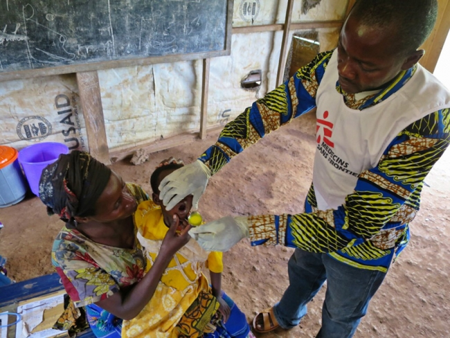 A little girl is given her first dose of malaria medication