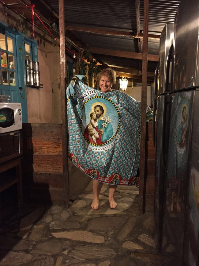 The brightly printed fabric is teal in colour, with a maroon leaf pattern and a large image of a saint in the middle, holding a bunch of lillies