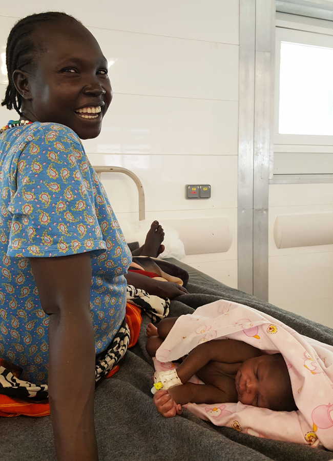 A mother smiles with her baby in the new hospital