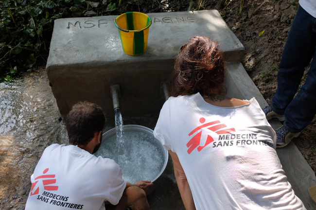 Image shows an MSF team repairing a water pump in the village of Limozia, DRC