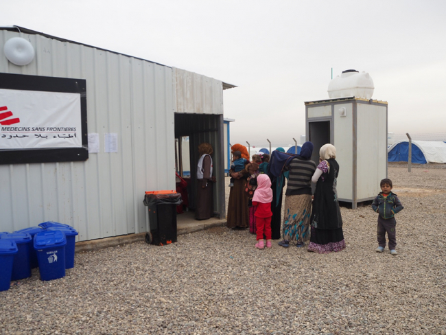 A queue of women and children wait outside a corregated metal building with an MSF logo on the wall