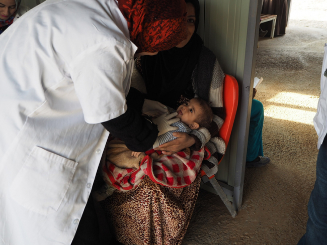 A baby cries as a member of MSF medical staff examines them.