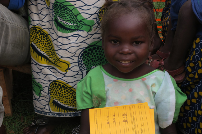 A little girl proudly holds her vaccination card