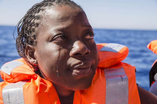 A single tear trickles down the cheek of a woman who has been rescued