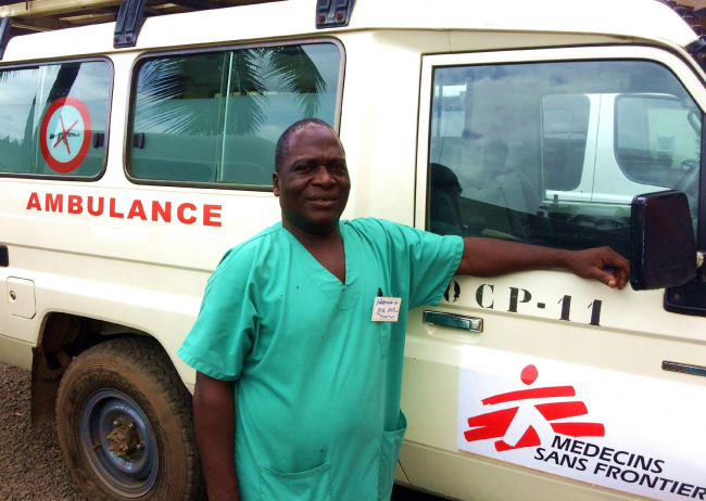 Image shows Richard, a smiling man in green scrubs, photographed at the MSF / Doctors without Borders hospital in liberia