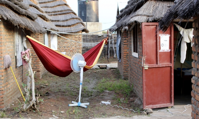 Someone lies in a hammock with an electric fan blowing as they try to keep cool outside.