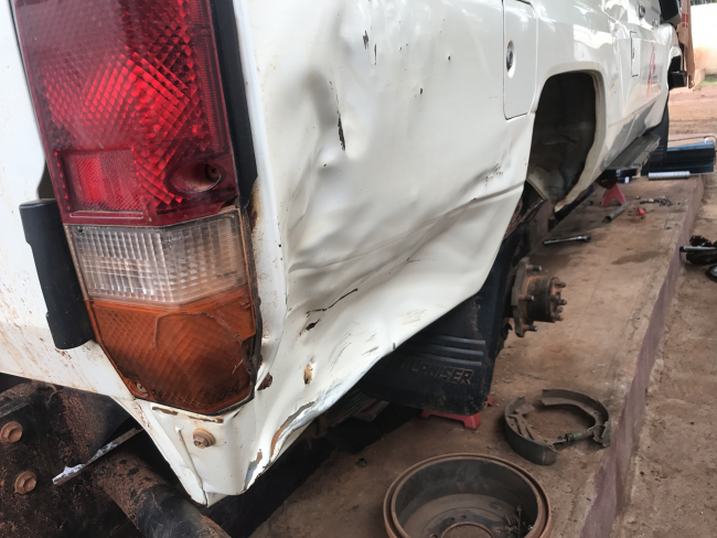 Image shows a very dented car