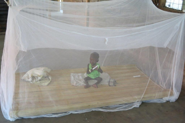 A malnourished child sits beneath the protection of a mosquito net in Leer hospital.