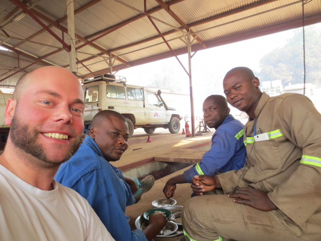 Image shows Holger and the other mechanics enjoying a snack at the MSF auto workshop in Bangui, Central African Republic