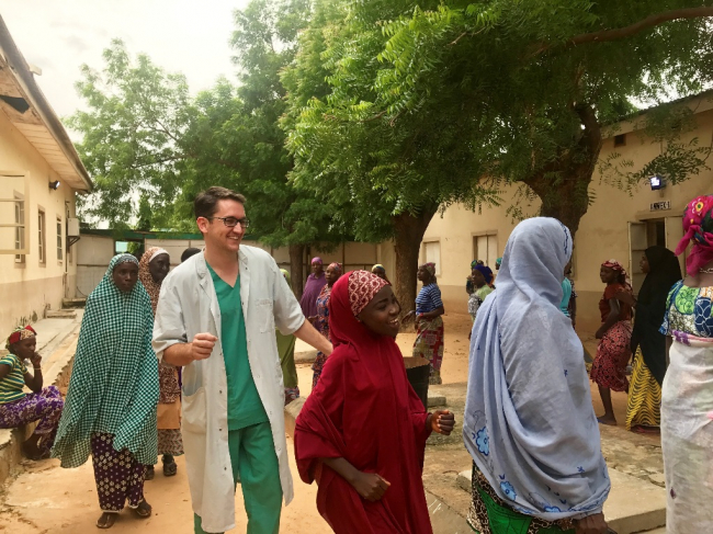 Image shows Jared, a tall man in a white doctors' coat and green scrubs, smiling as he dances with brightly dressed women
