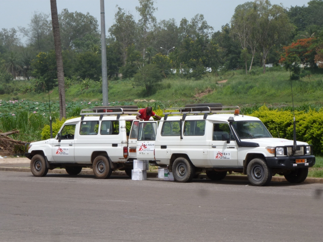 Image shows two MSF land cruiser cars back to back, transferring patients between the two