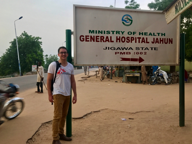 Image shows Jared, who wears an MSF t-shirt and glasses, standing next to the sign for Jahun General Hospital