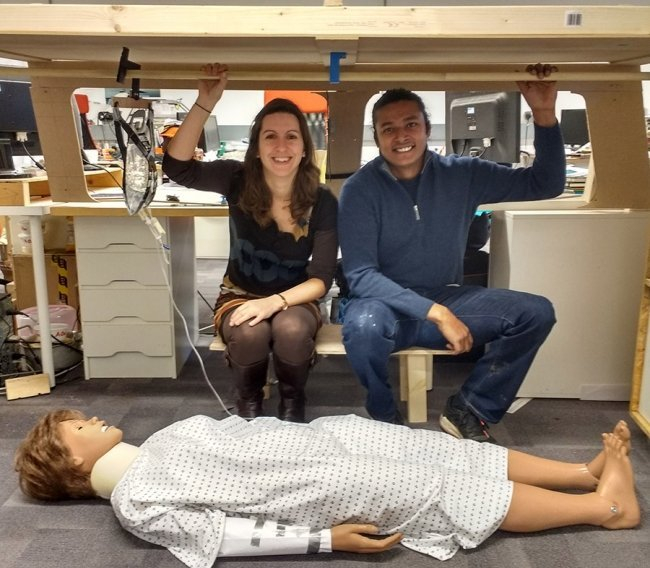 A woman and a man sit together by a dummy dressed as a patient in a wooden model of a land cruiser