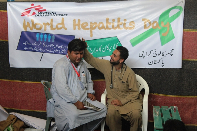Two staff members in front of the World Hepatitis Day banner