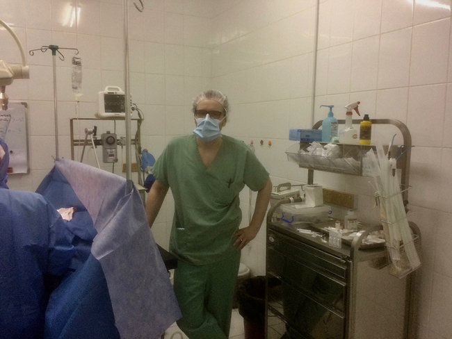 Anaesthetist Kariantti at work in the MSF/Doctors without Borders operating theatre in Khameer, Yemen. He wears green scrubs and a surgical mask