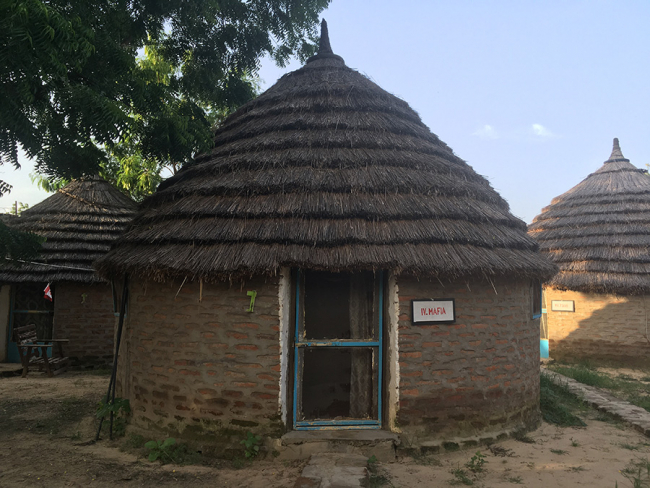 Image shows a round hut built of mud bricks with a grass roof