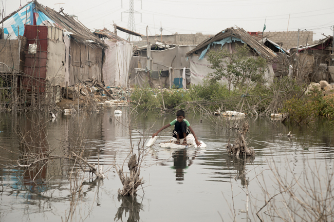 A boy floats on a make-shift raft in a flooded area of Machar Colony, Pakistan