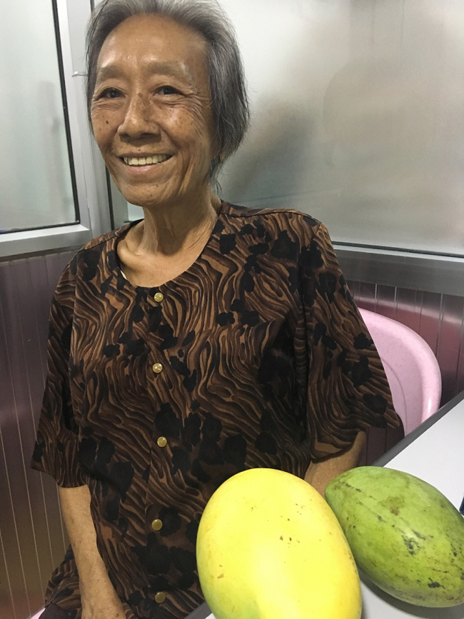 A woman smiles next to two enormous mangoes in the MSF hepatitis C clinic in Phnom Penh