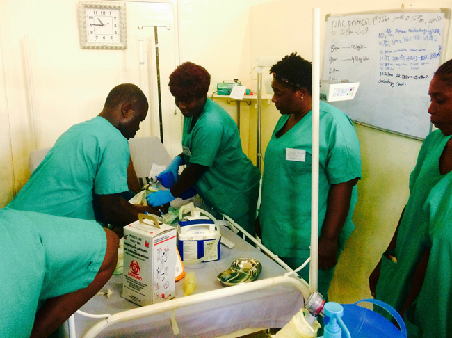 A team of health care staff in green scrubs resuscitate a baby