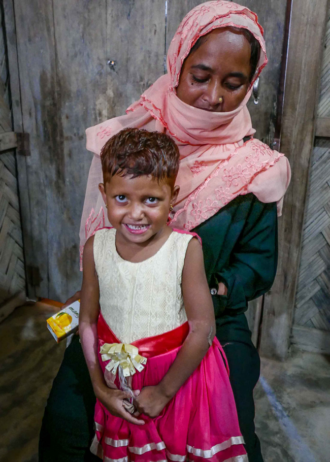 Image shows a little girl and her mum, who holds a box of mango sweets