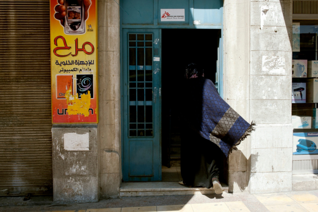 Image shows a woman wearing a blue scarf, entering the MSF/Doctors Without Borders non-communicable diseases clinic in Irbid, Jordan.