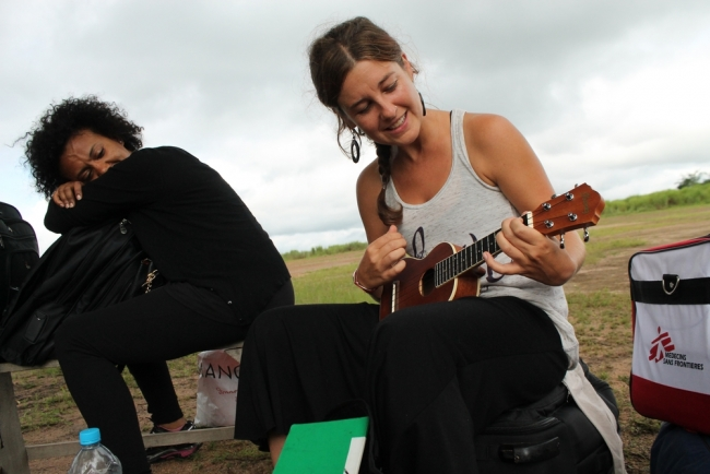 While waiting for the MSF car to pick up the team from Kissidougou airstrip, American nurse Carissa Guild plays the ukulele to pass the time.