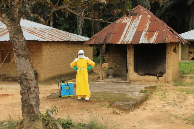 A sprayer takes a break from disinfecting houses.