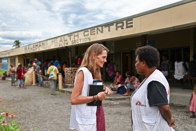 Two women in MSF jackets talk in front of a health centre