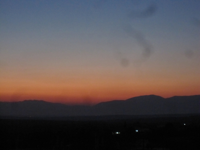 smoke rises in the sky over the Syrian mountains