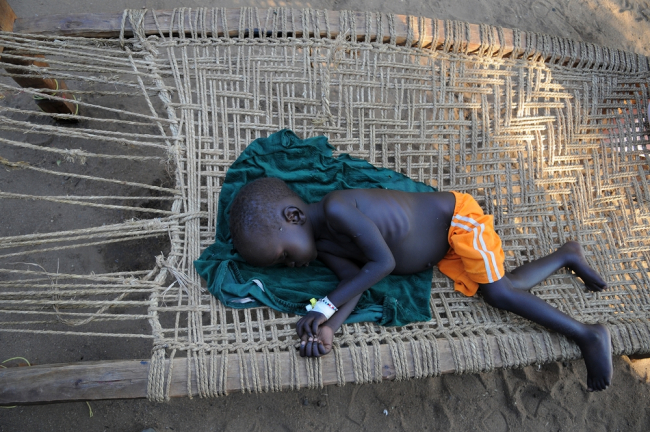 A young boy wisely chooses to sleep in the shade outside the field hospital.