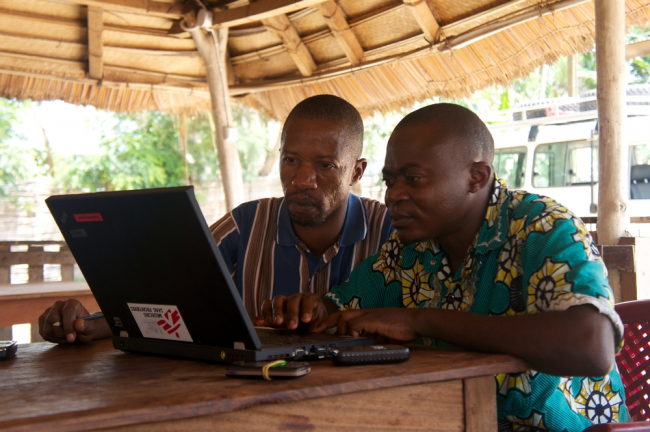 Two men work at a laptop with an MSF logo on it.