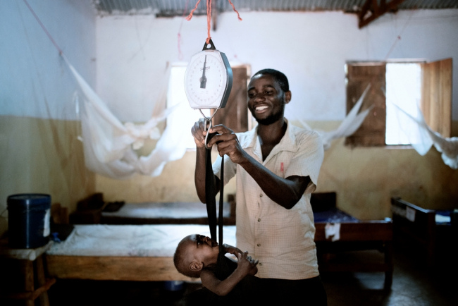 A member of MSF staff weighs a baby at a therapeutic feeding centre in Tanzania