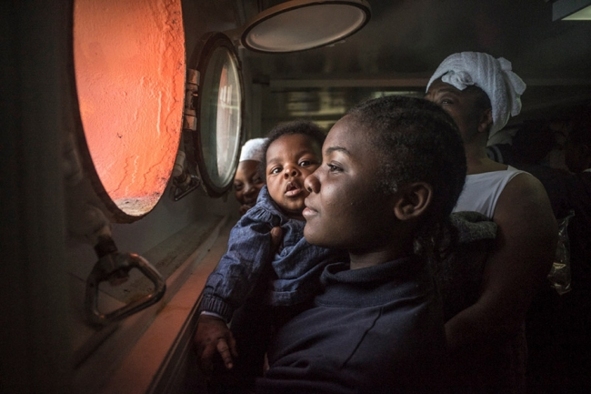 A woman and her baby look out the porthole of the Aquarius
