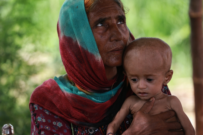 A woman holds a malnourished child in Balochistan, Pakistan